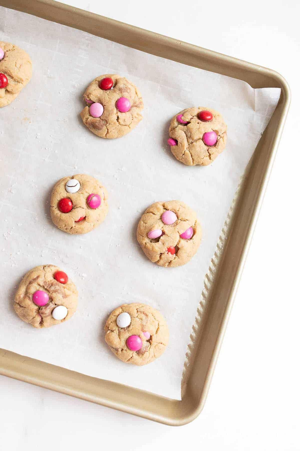 Gold baking sheet filled with Valentine's m and m cookies.