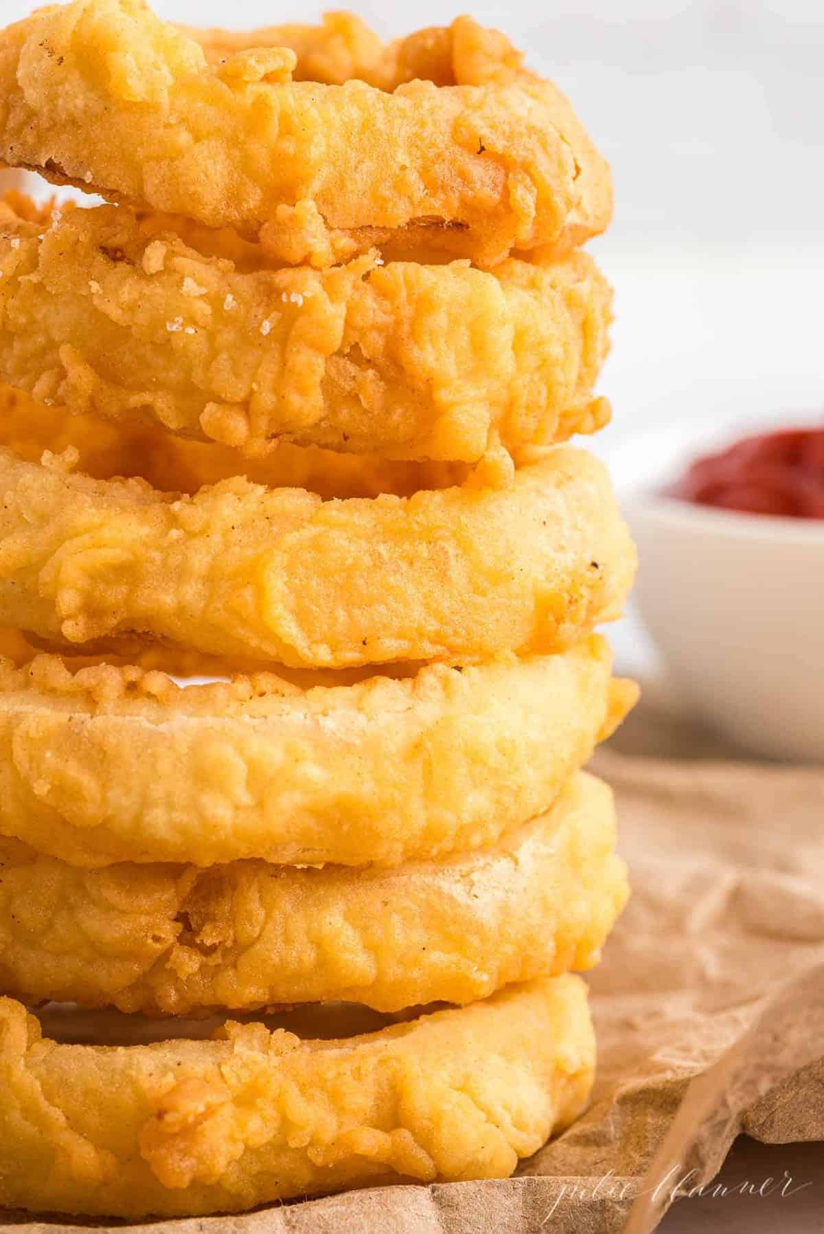 Stack of homemade onion rings on a piece of butcher paper, bowl of ketchup in the background.