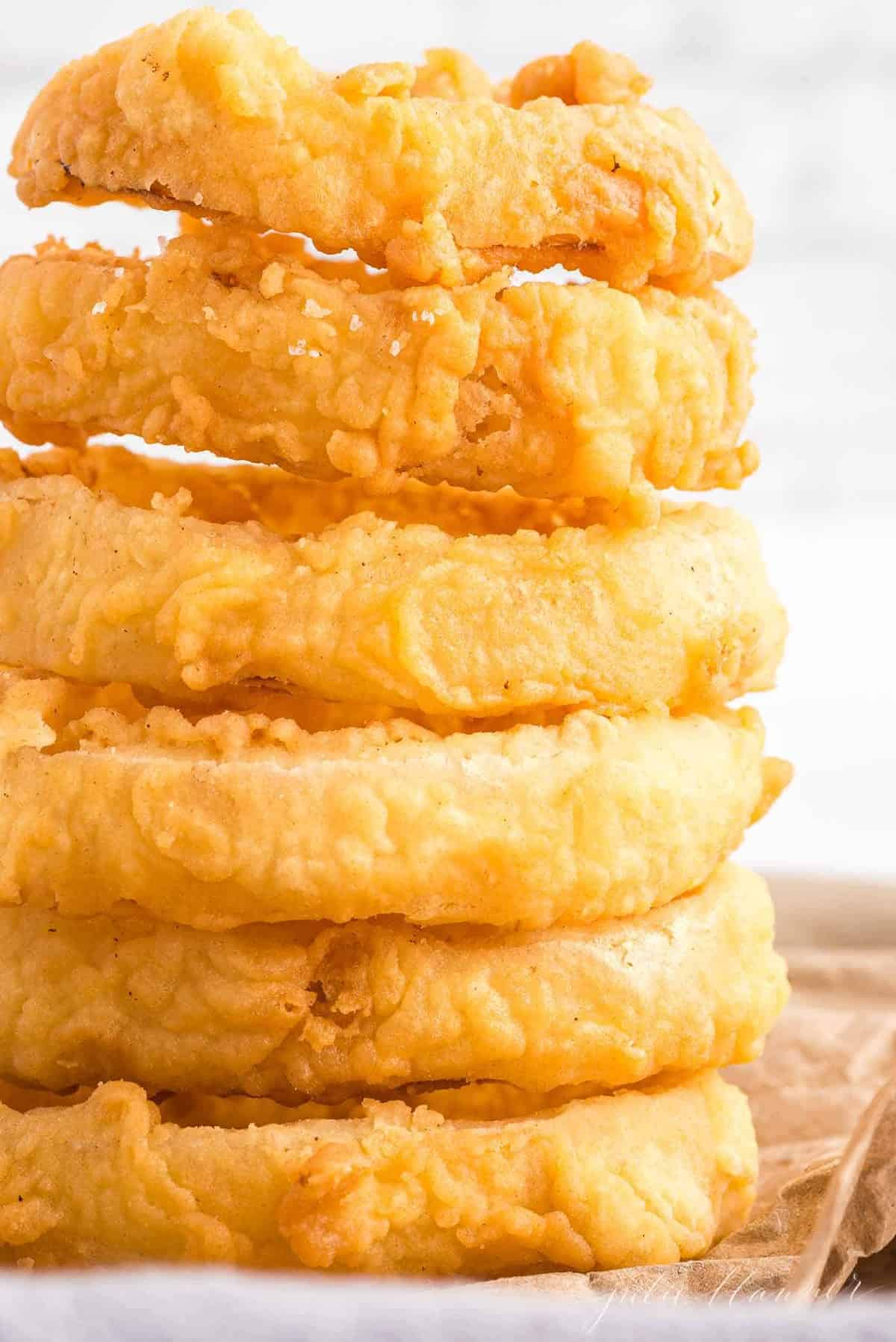 Stack of homemade onion rings on a piece of butcher paper.