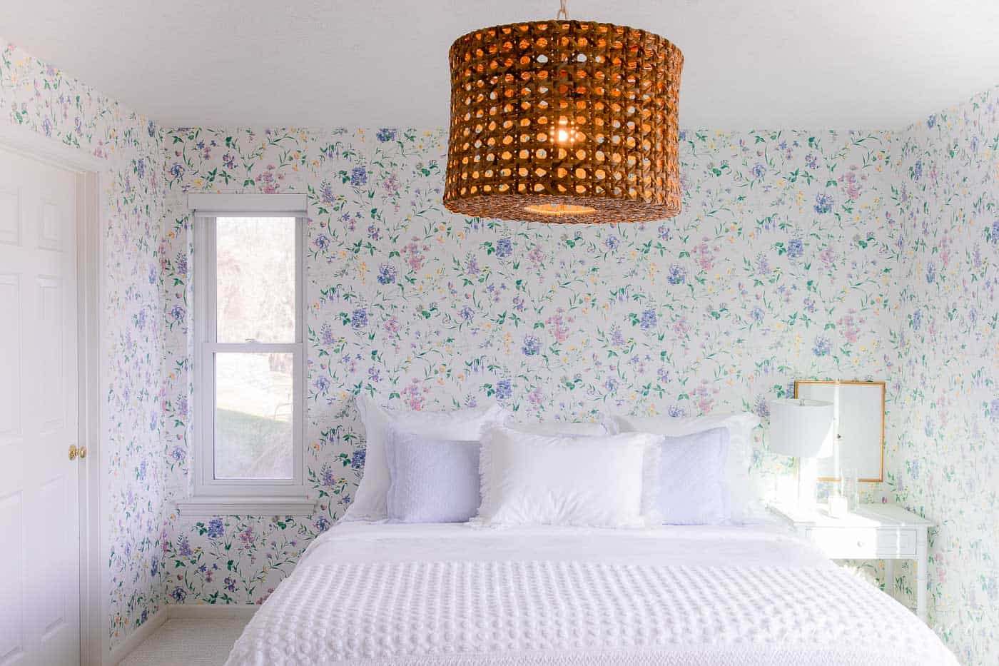A cottage bedroom with white bedding, floral wallpaper, and a small window with a custom roller shade.