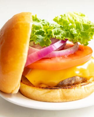 White background with a white plate featuring a classic cheeseburger, stacked with cheese, tomato, onion and lettuce, top bun to the side.