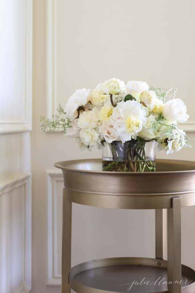A fresh floral arrangement of herbs and peony flowers on an antique gold accent table..