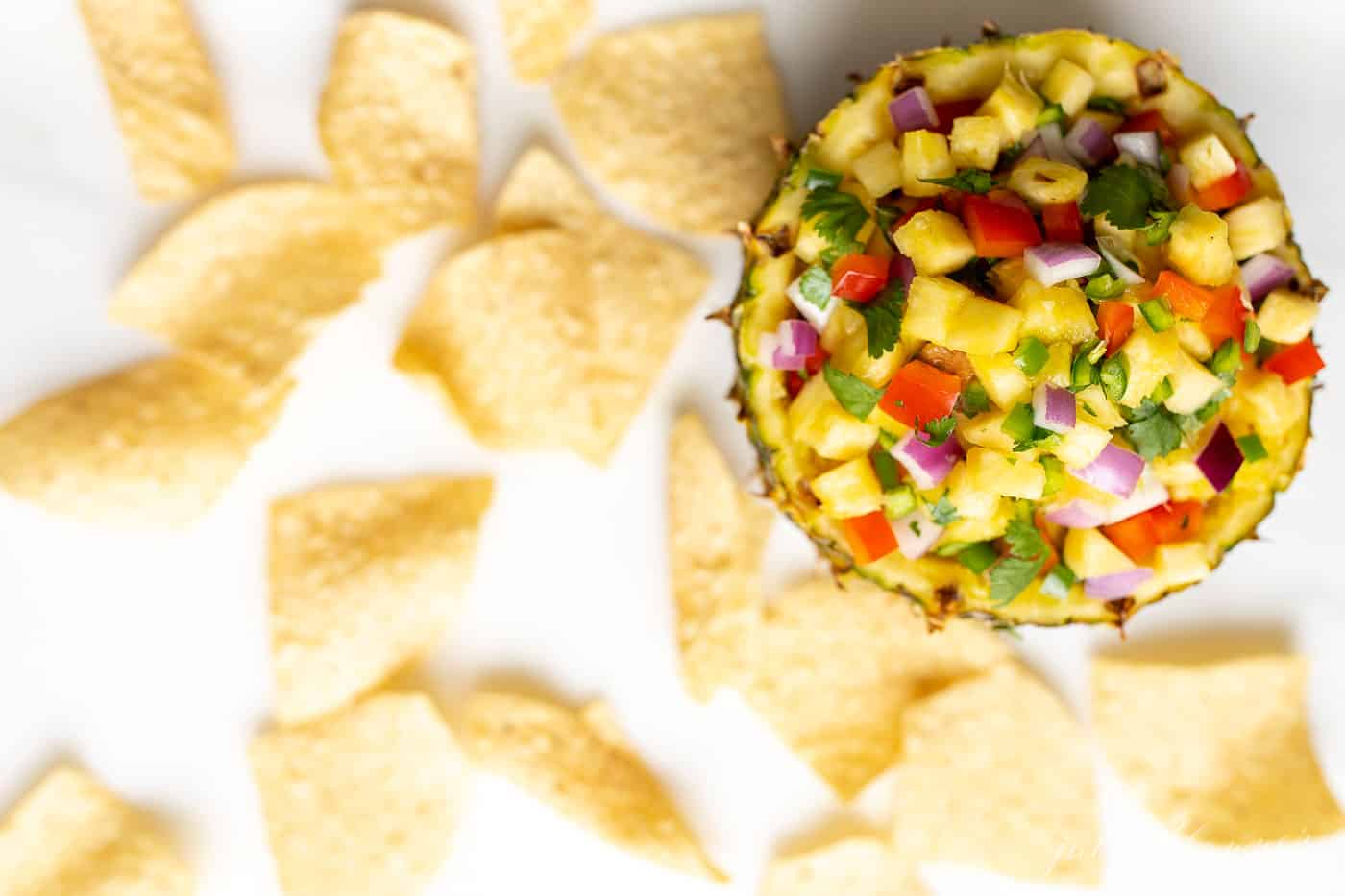 Pineapple salsa in a pineapple bowl, surrounded by tortilla chips.