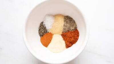 A white bowl with a blend of seven spices to make blackened seasoning.