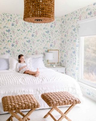A white bedroom with floral wallpaper accents, a little girl sitting on the bed.
