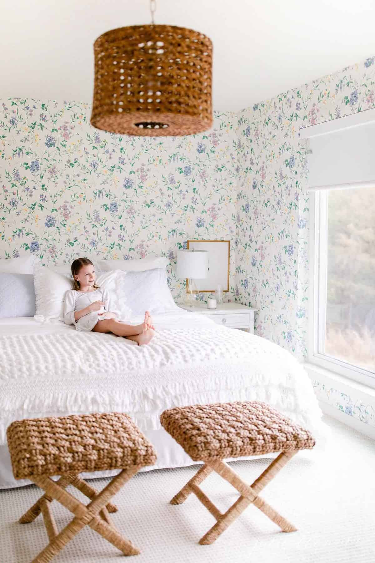 Floral wallpapered bedroom, a little girl lies on the bed with a remote for a motorized roller shade.