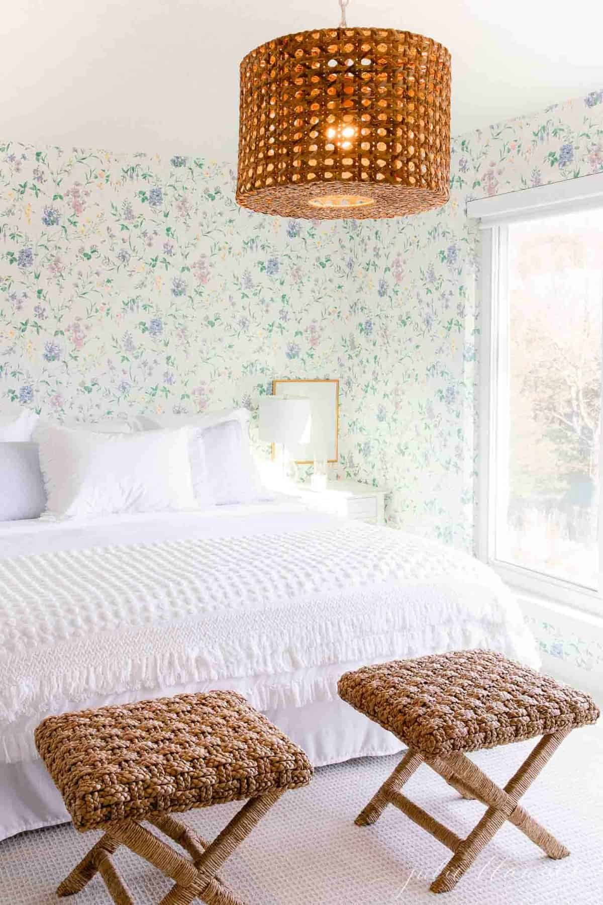A cottage bedroom with white bedding, floral wallpaper, and a big window with a blackout shade.