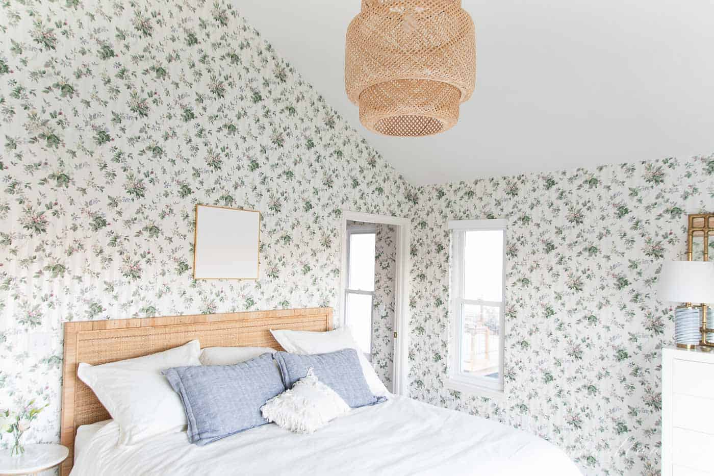 A cottage bedroom with white bedding, floral wallpaper, and a big window with a modern window treatment roller shade.