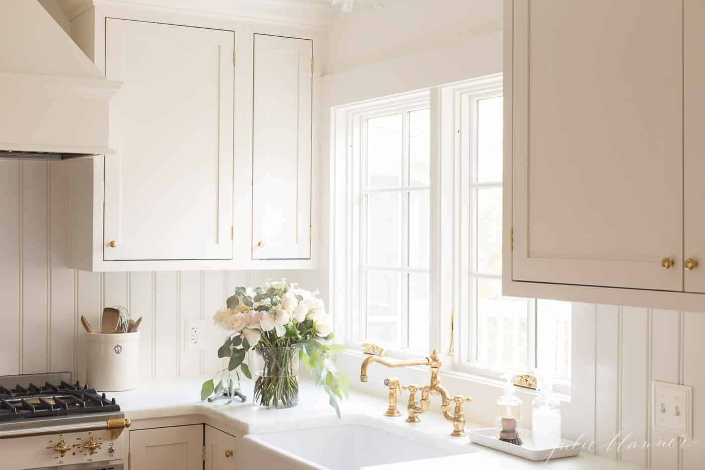 A white kitchen with a farmhouse sink, brass kitchen faucet and a vase of flowers to the side.