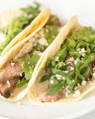White plate with three small carne asada tacos.
