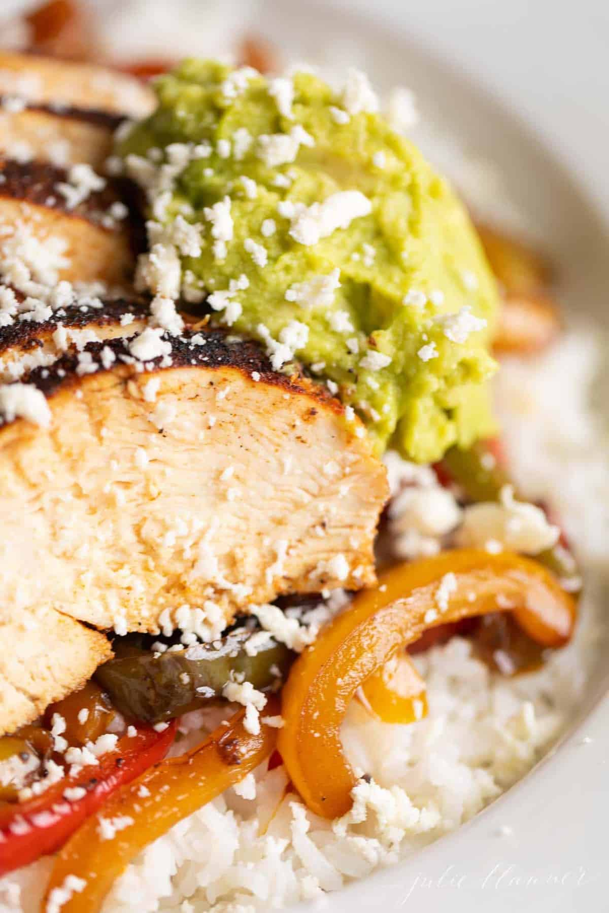 Close up of a chicken fajita bowl, crumbled cheese and guacamole on top.