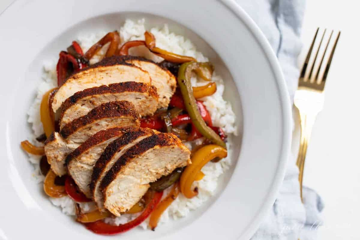 A bowl of chicken over rice, peppers layered in between.