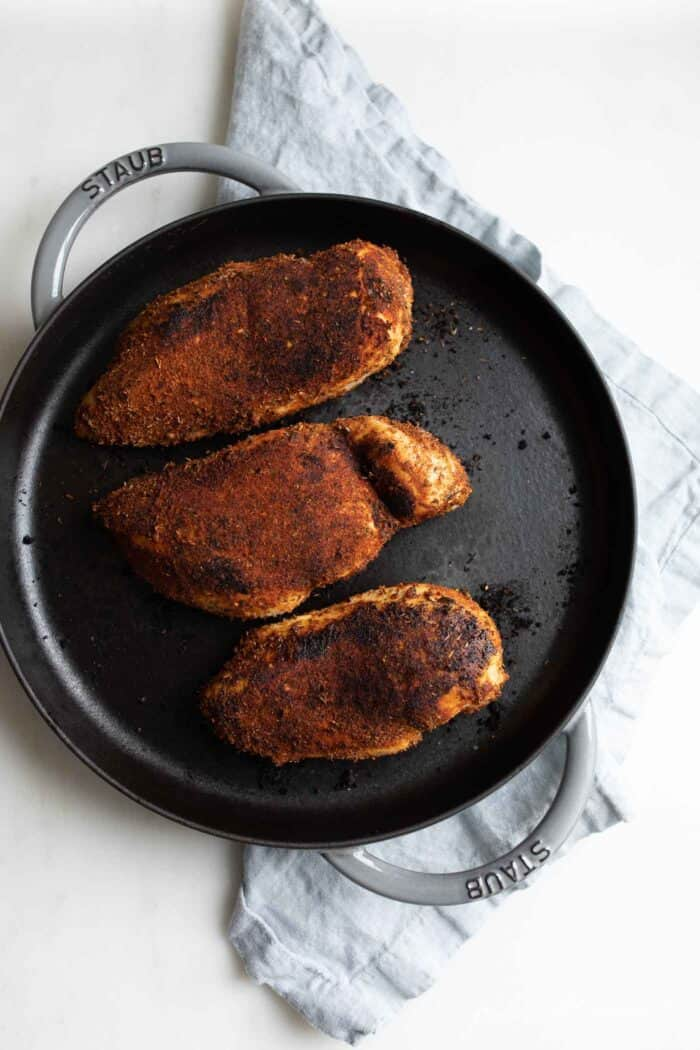 A cast iron pan with three blackened chicken breasts.