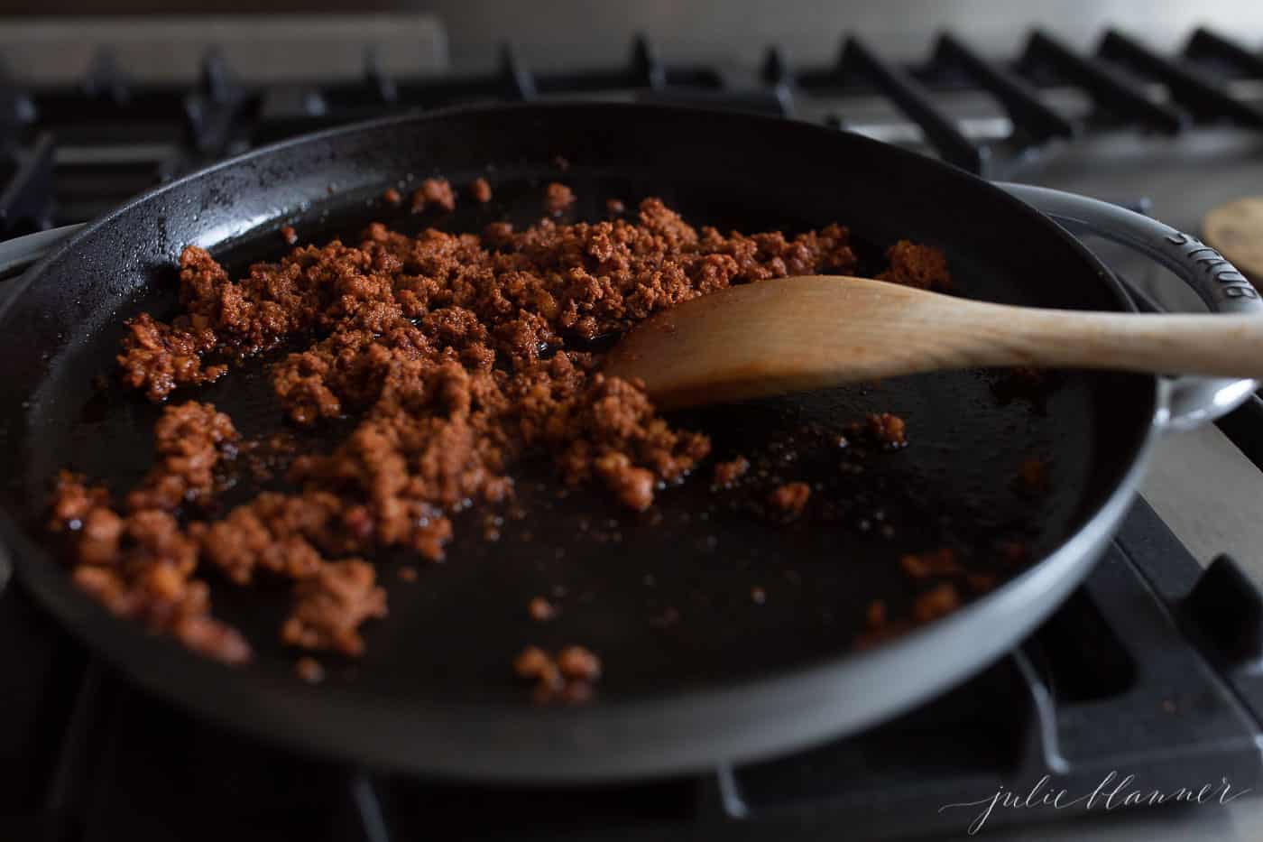 A frying pan filled with crumbled chorizo on the stove, wooden spoon to the side.