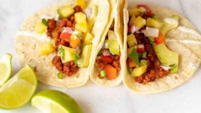 Three corn tortillas on a white surface, chorizo taco ingredients in each one.