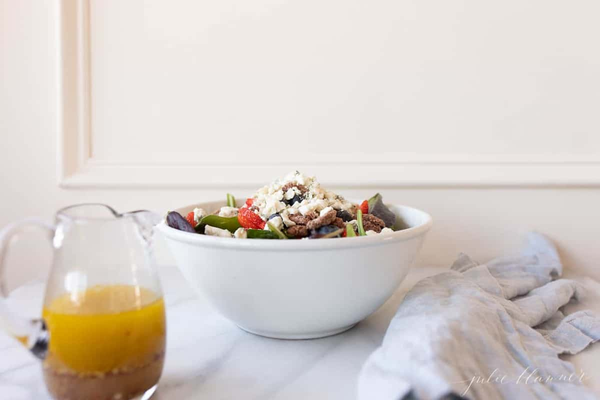 A bowl of spring mix salad, dressing in a clear pitcher to the side.
