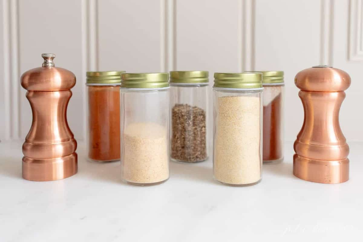 A white background with glass bottles of spices preparing to make blackened chicken seasoning.