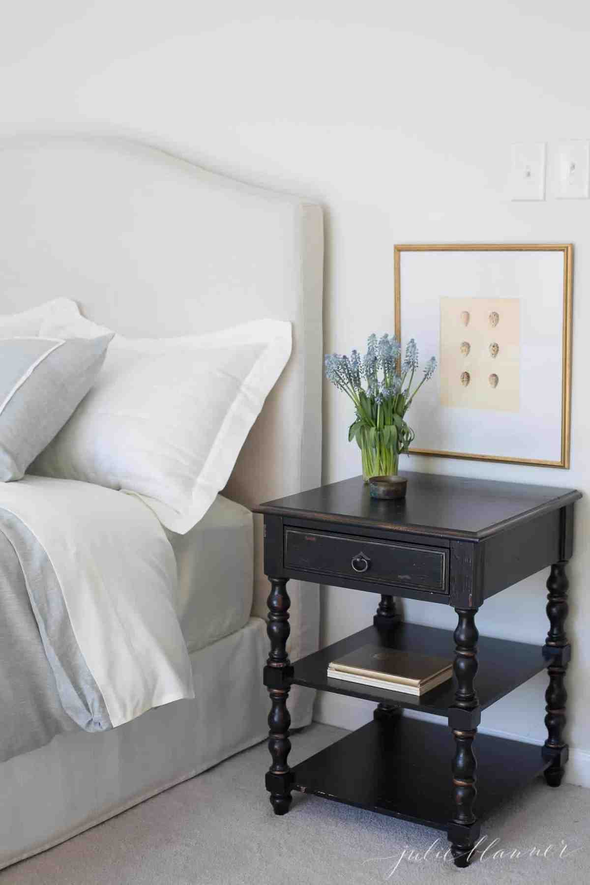 A white bedroom with spring decor additions like a vase of flowers and a fresh spring art print.