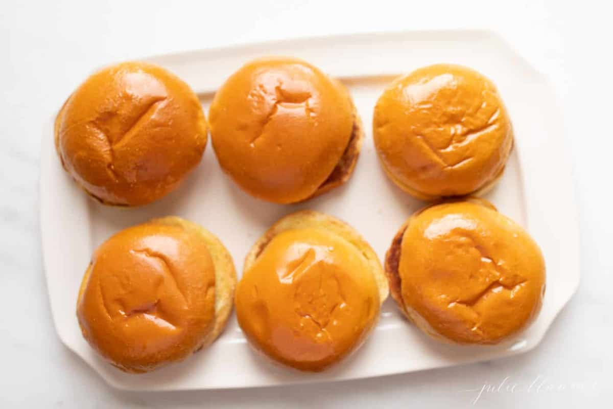 White plate with six burger buns waiting for gourmet burgers.
