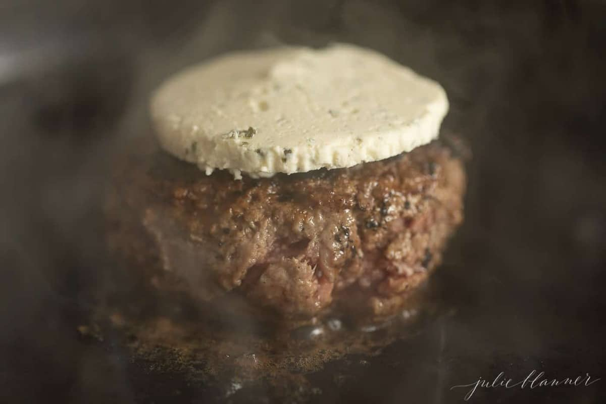 A burger in a cast iron pan, cooking with boursin cheese melting on top.