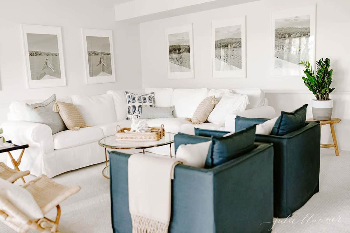 A navy and white modern living room with a sectional sofa piled with decorative pillows.