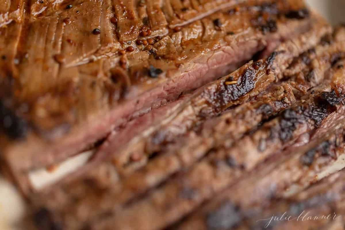 A close up of sliced flank steak after being cooked on the stove.