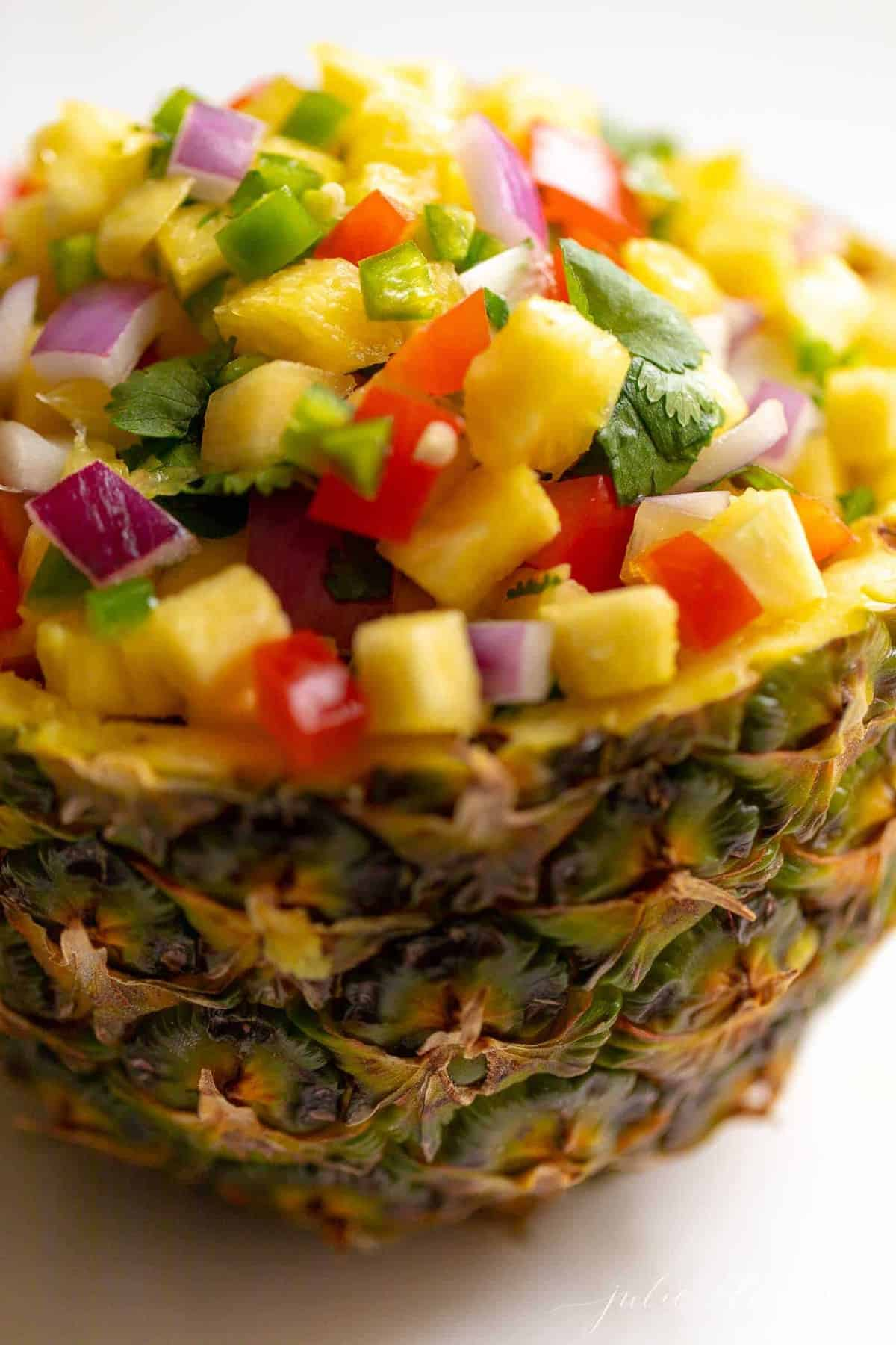 A fresh bowl made from a cut pineapple, filled with pineapple salsa.