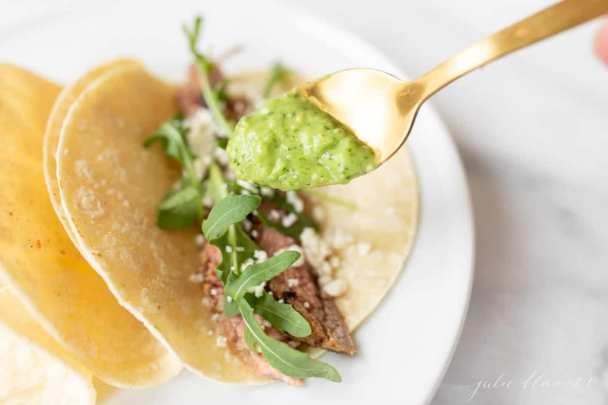 A white plate with steak tacos, spoon full of an avocado salsa recipe to add to the top.