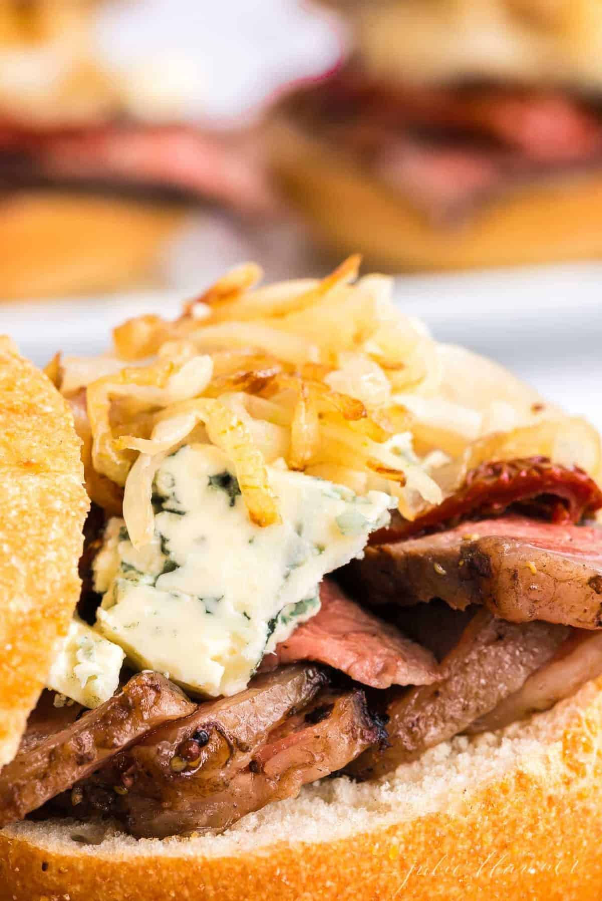 A steak sandwich with onion straws and cheese on top, top bun balanced to the side.