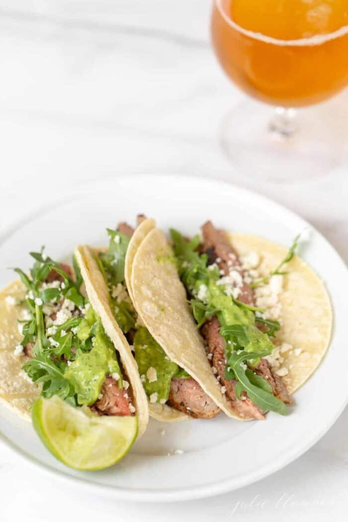 Carne asada tacos on a white plate.
