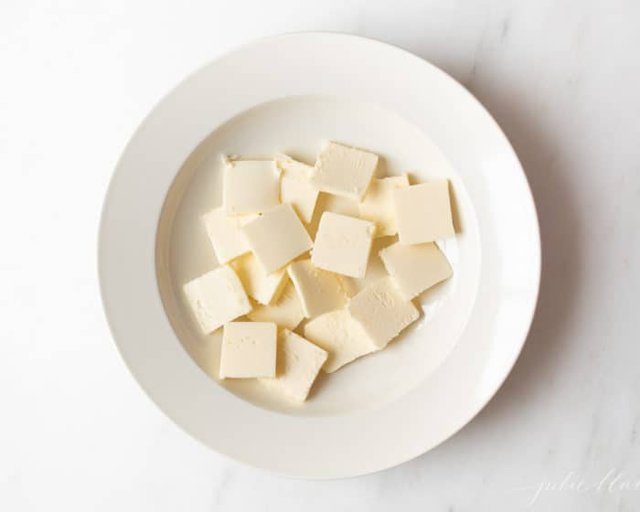 A white surface, with a white plate full of cuts of cold butter.