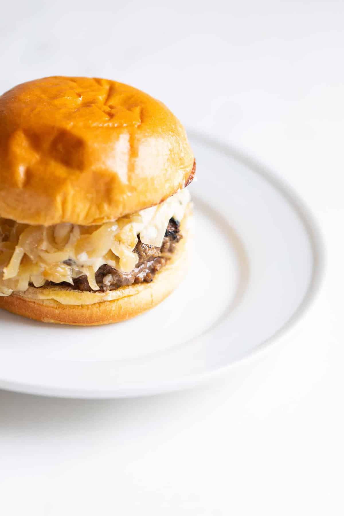 White surface, white place featuring a gourmet burger on a brioche bun.