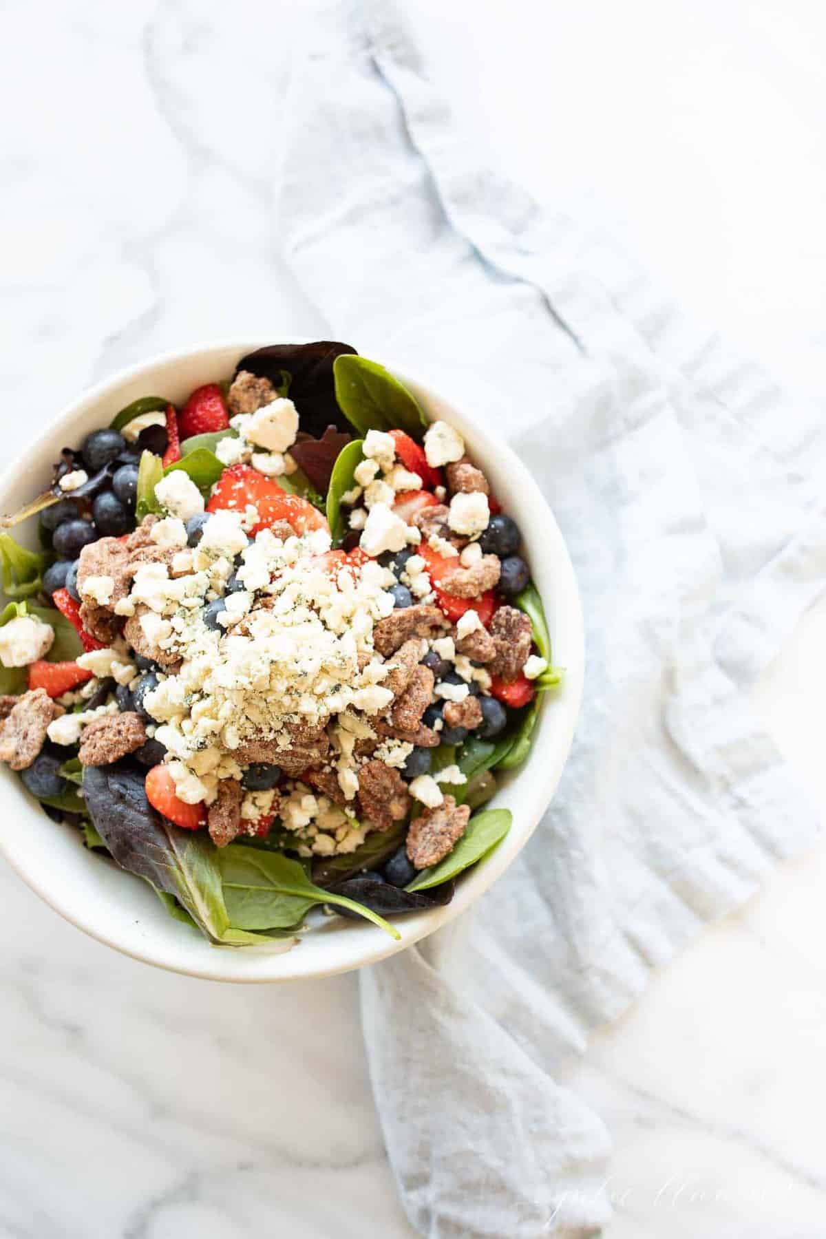 A white bowl full of a fresh spring mix with berries and nuts