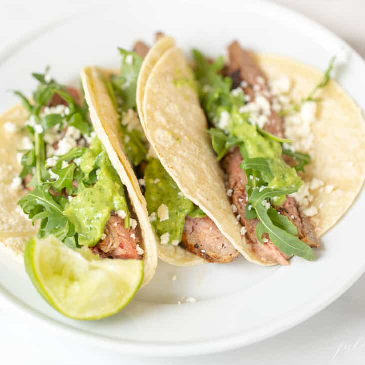 Carne asada tacos, topped with cilantro on a white plate.