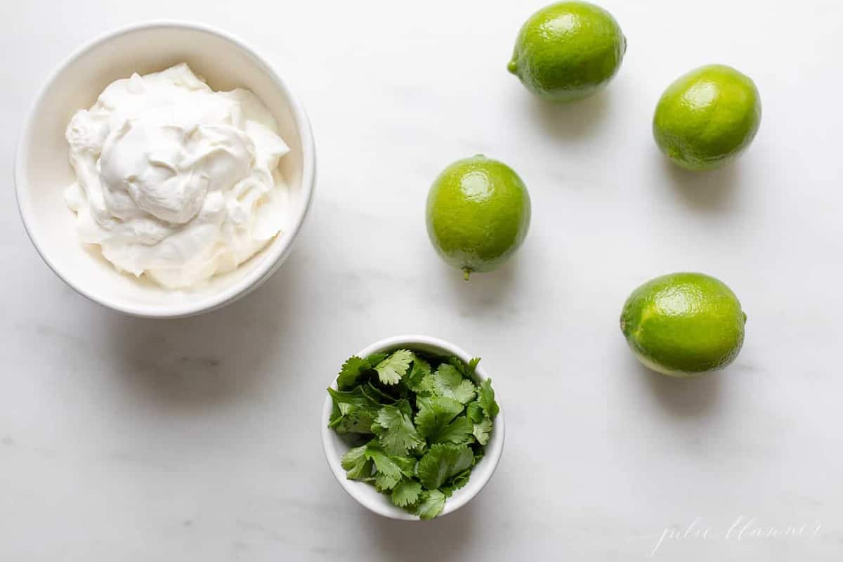White surface with whole limes, bowl of cilantro and bowl of sour cream.