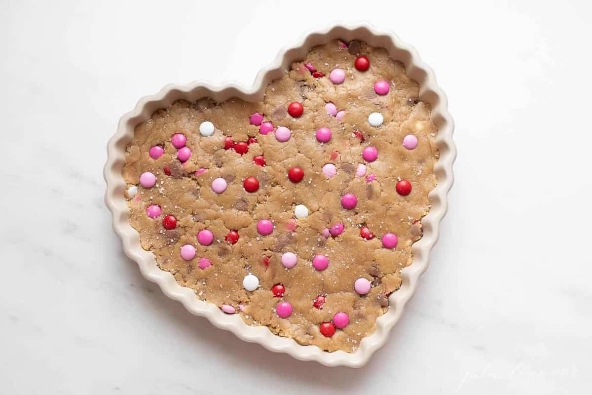 Thick and Chewy M&M Cake in a heart shaped dish, topped with Valentine\'s Day M&Ms.