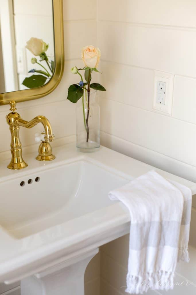 A white pedestal bathroom sink with a clear vase and a single bloom, towel hanging over the edge of the sink.