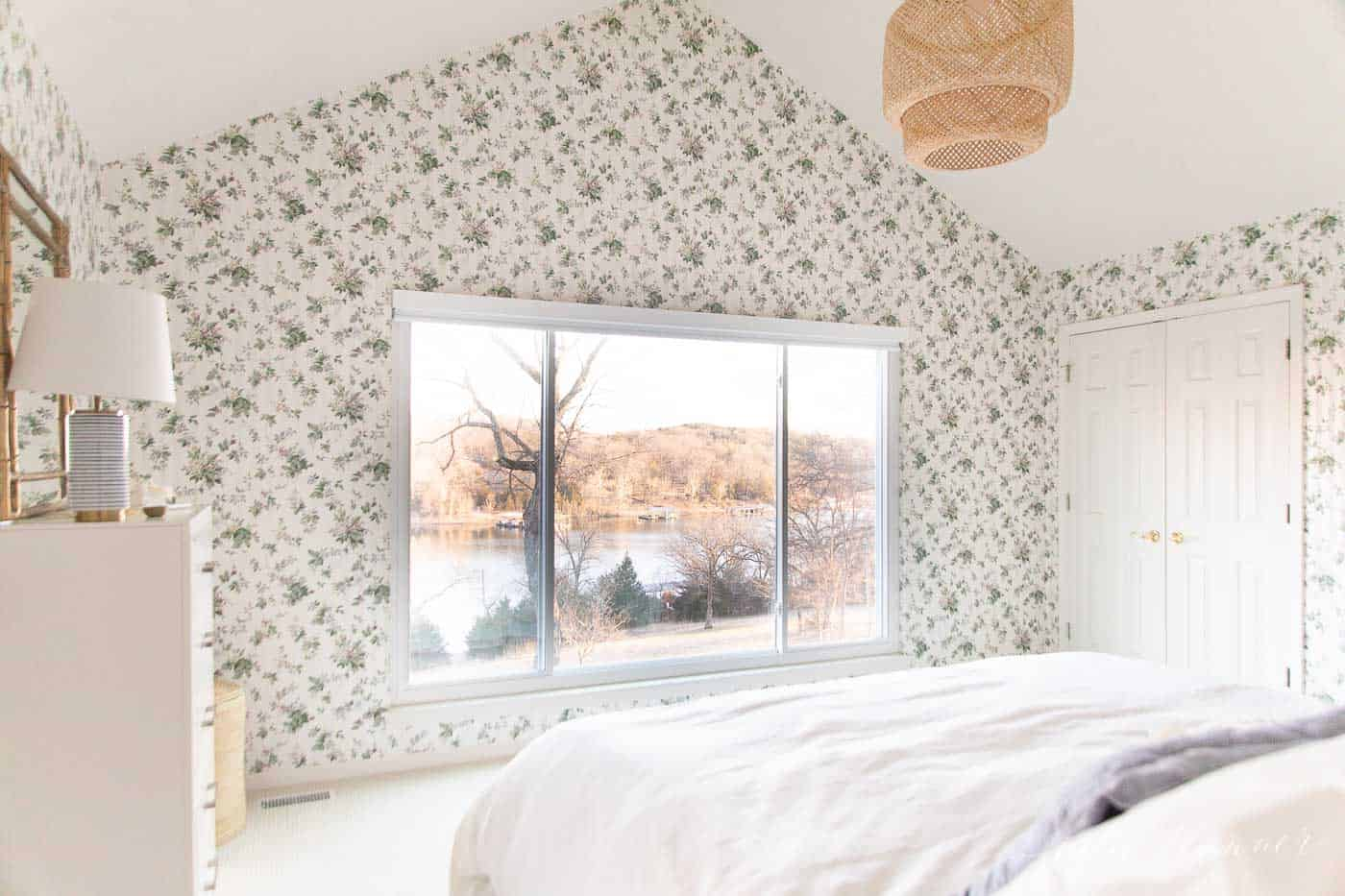 A cottage bedroom with white bedding, floral wallpaper, and a big window with a blackout roller shade as window decor.