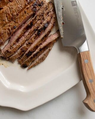 A flank steak after being pan fried on the stove, sliced, knife to the side.