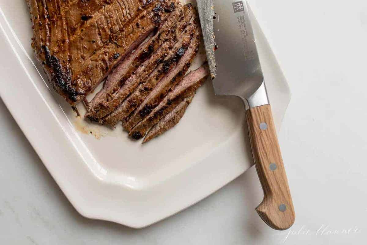 Steak being thinly sliced on a white platter.
