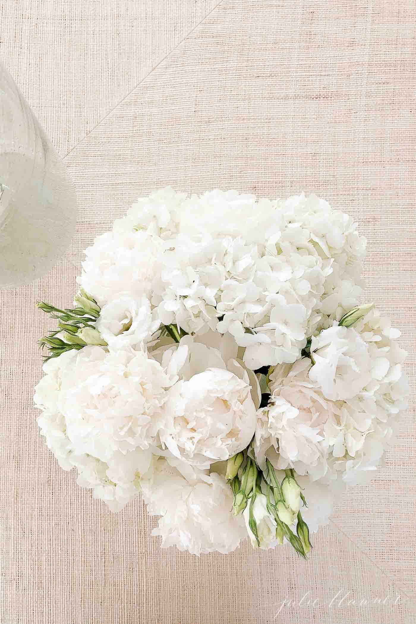 A fresh floral arrangement of white hydrangea and white peony flowers.