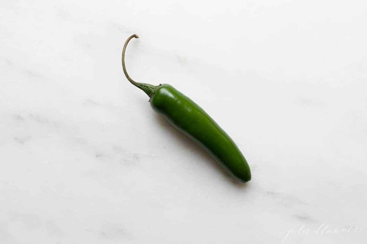 A marble surface with a single green jalapeno pepper.