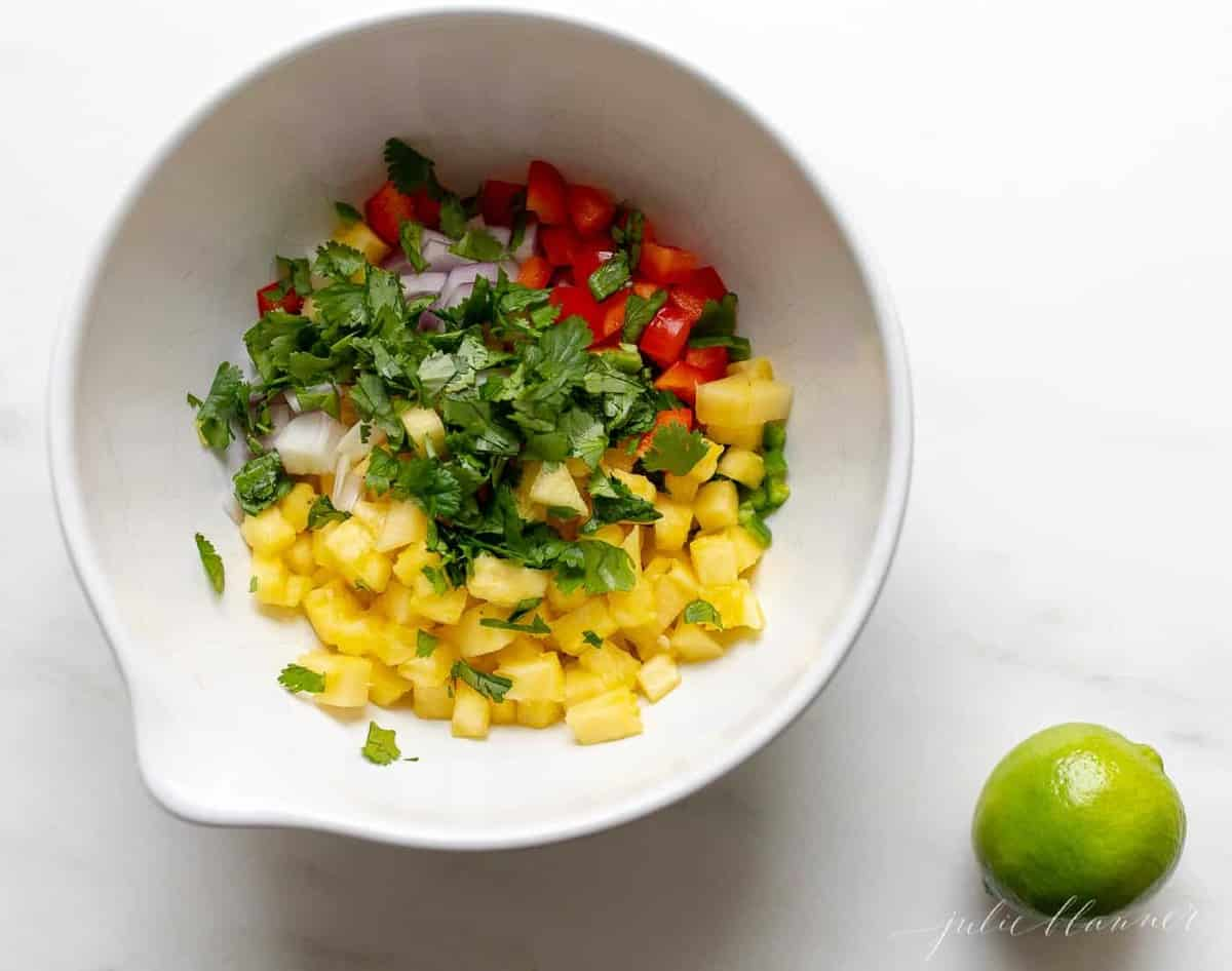 Pineapple salsa ingredients in a white bowl, with a lime to the side.