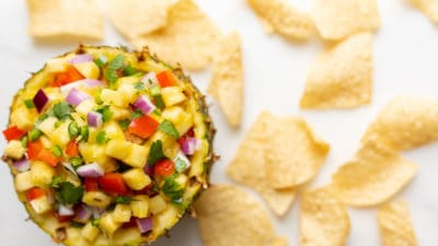 A fresh bowl made from a cut pineapple, filled with pineapple salsa, tortilla chips surrounding.