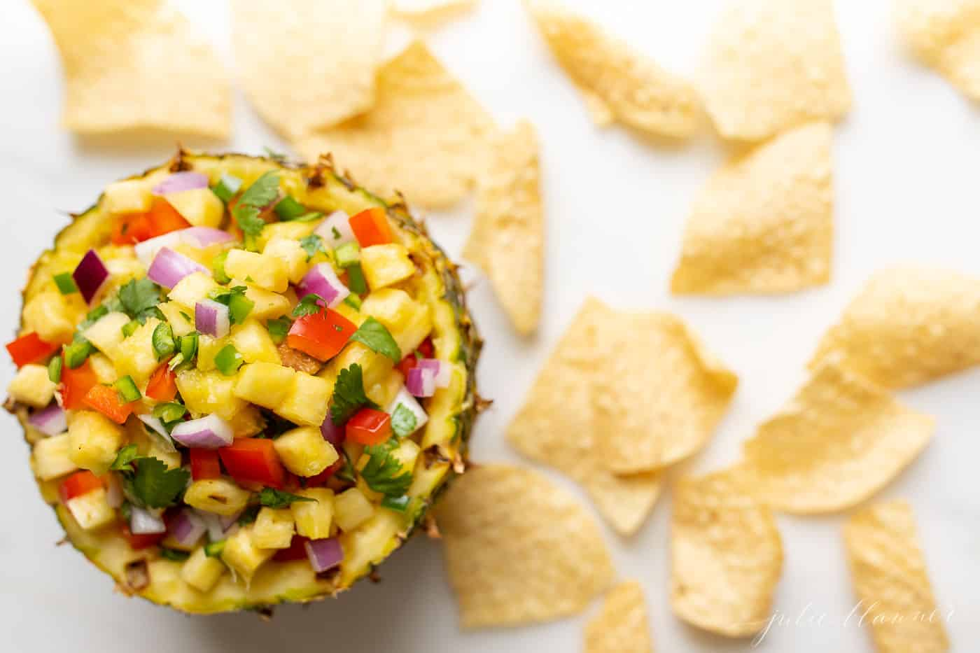 Corn salsa in a pineapple bowl, surrounded by tortilla chips.