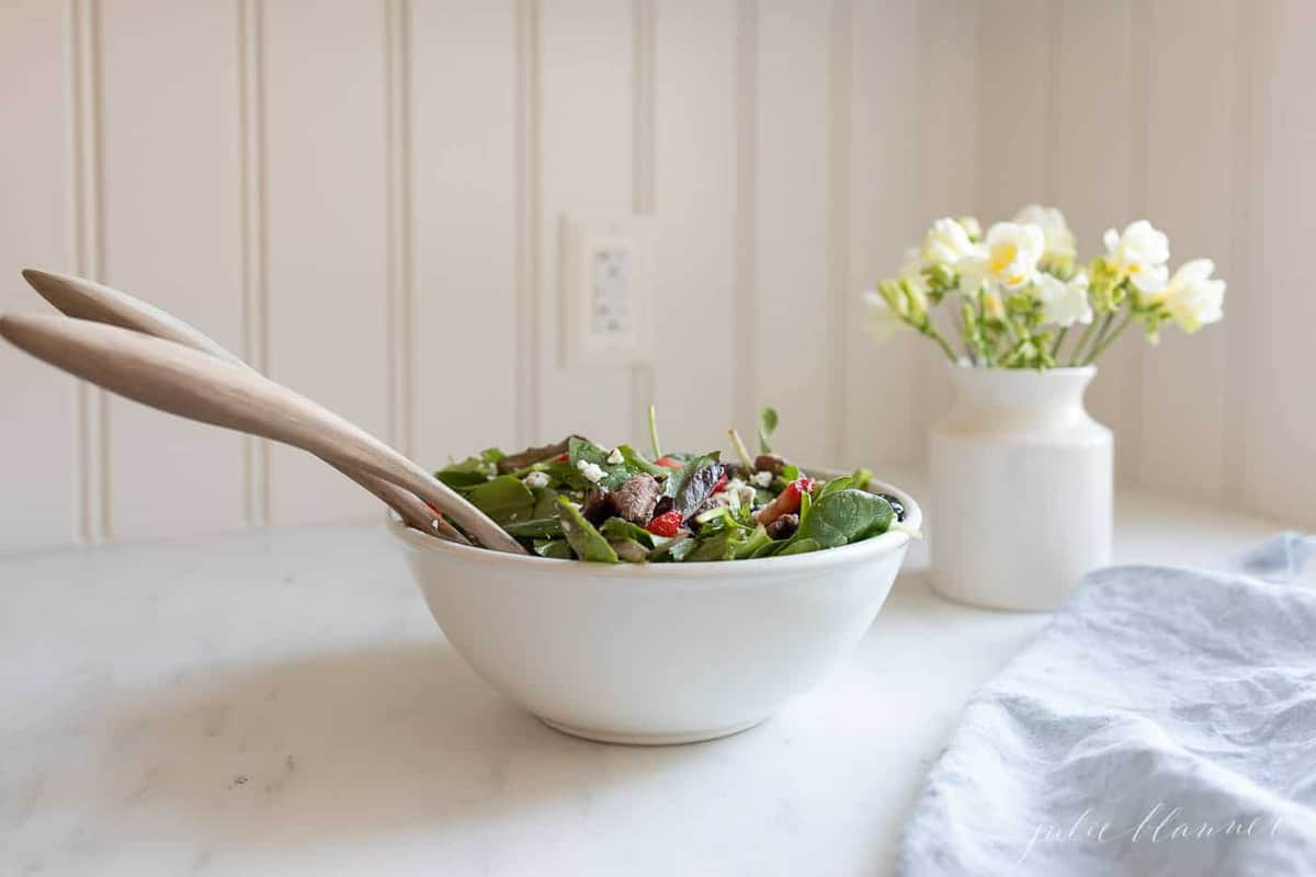 A white kitchen background, with a white bowl full of spring salad