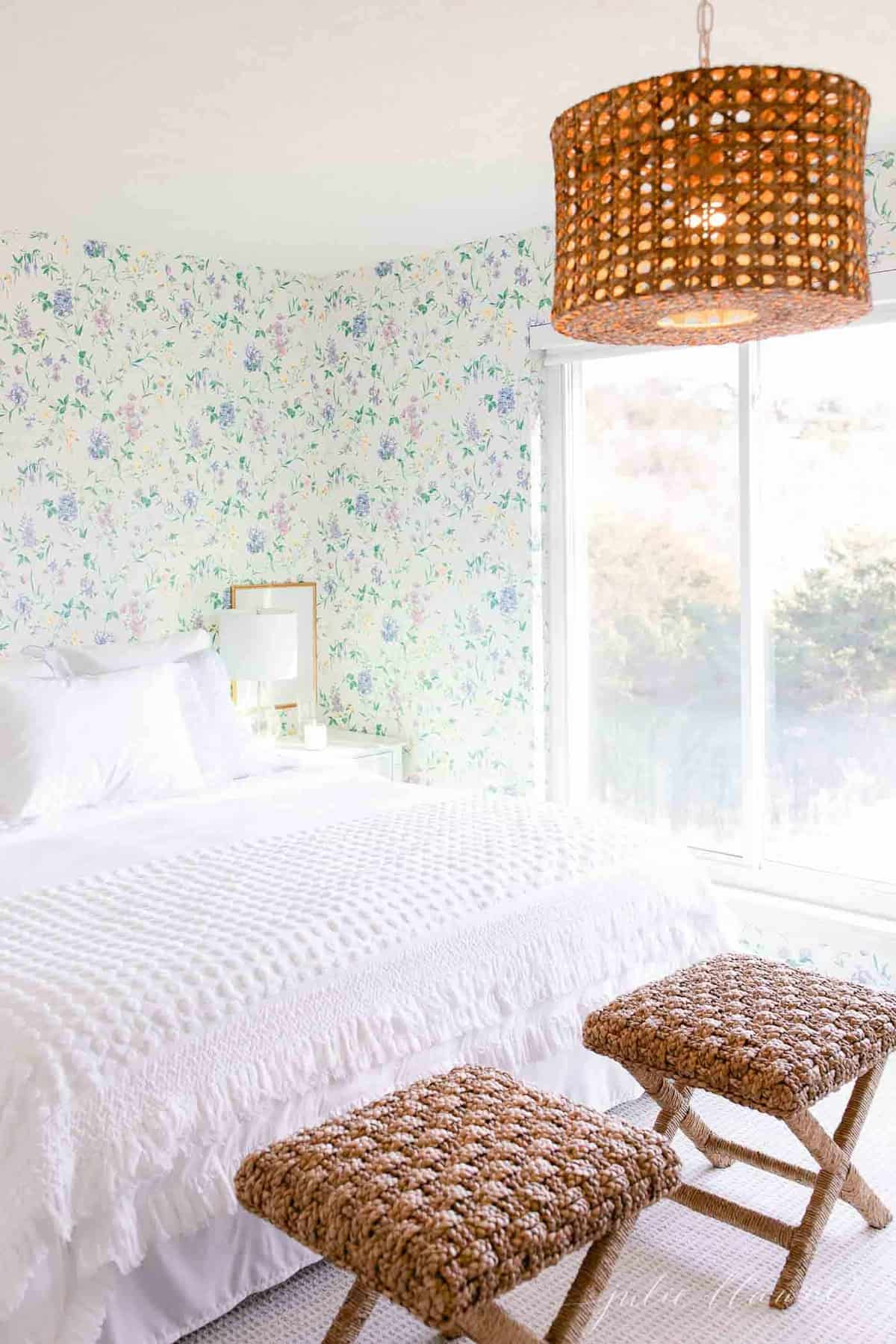 A cottage bedroom with white bedding, floral wallpaper, and a big window with a room darkening shade.