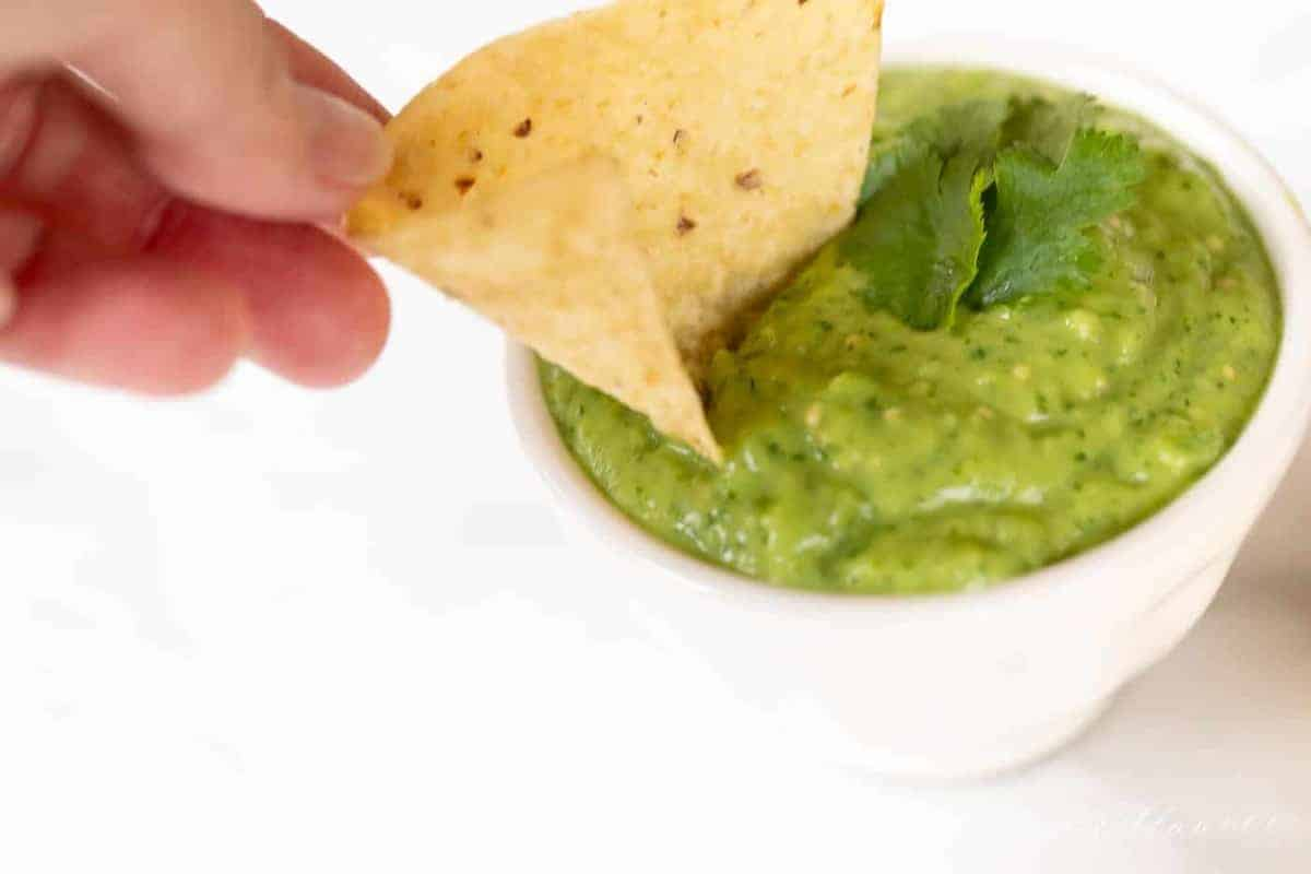A bowl full of avocado salsa, hand reaching in with a chip for dipping.