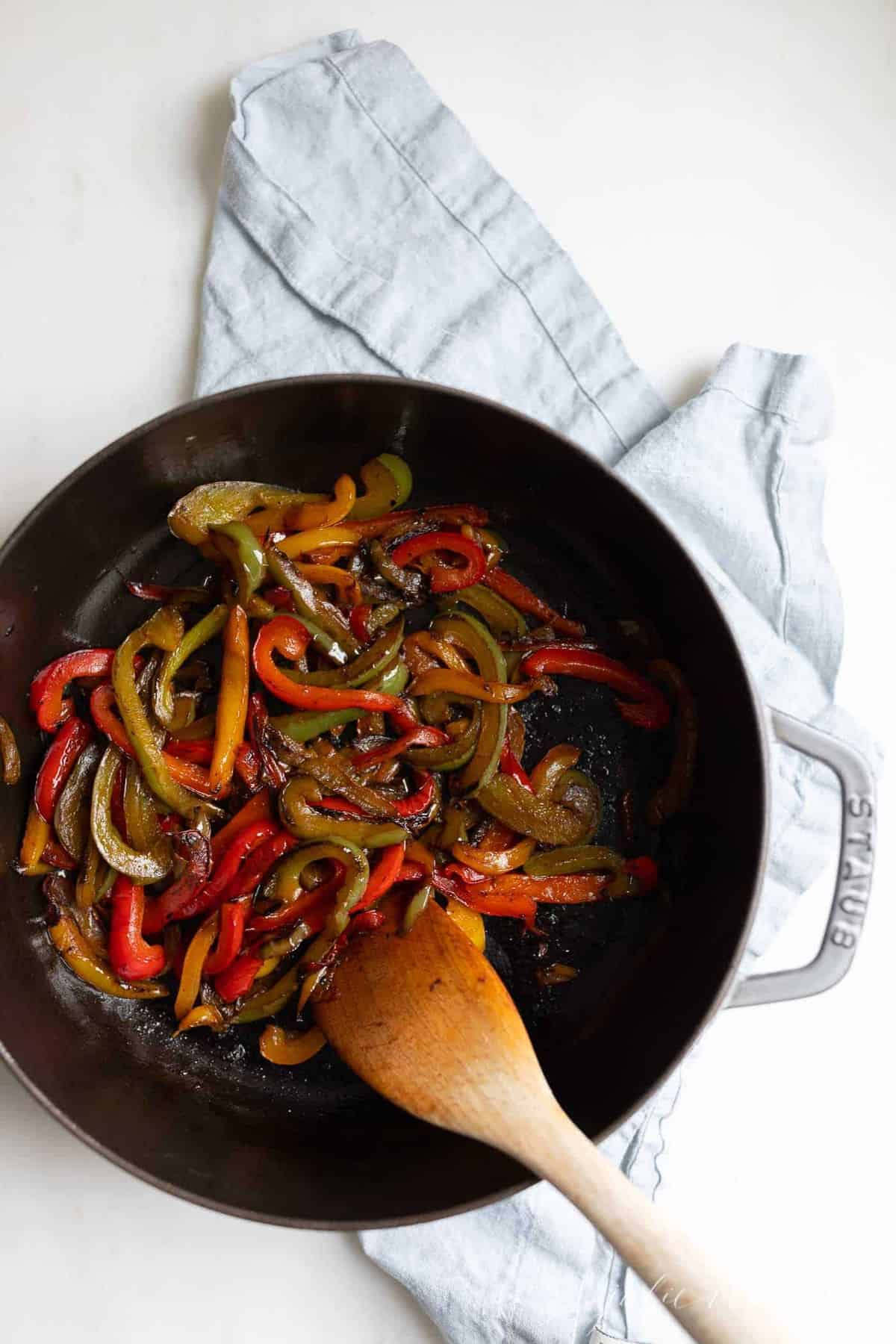 A cast iron pan full of sauteed bell peppers, wooden spoon to the side.