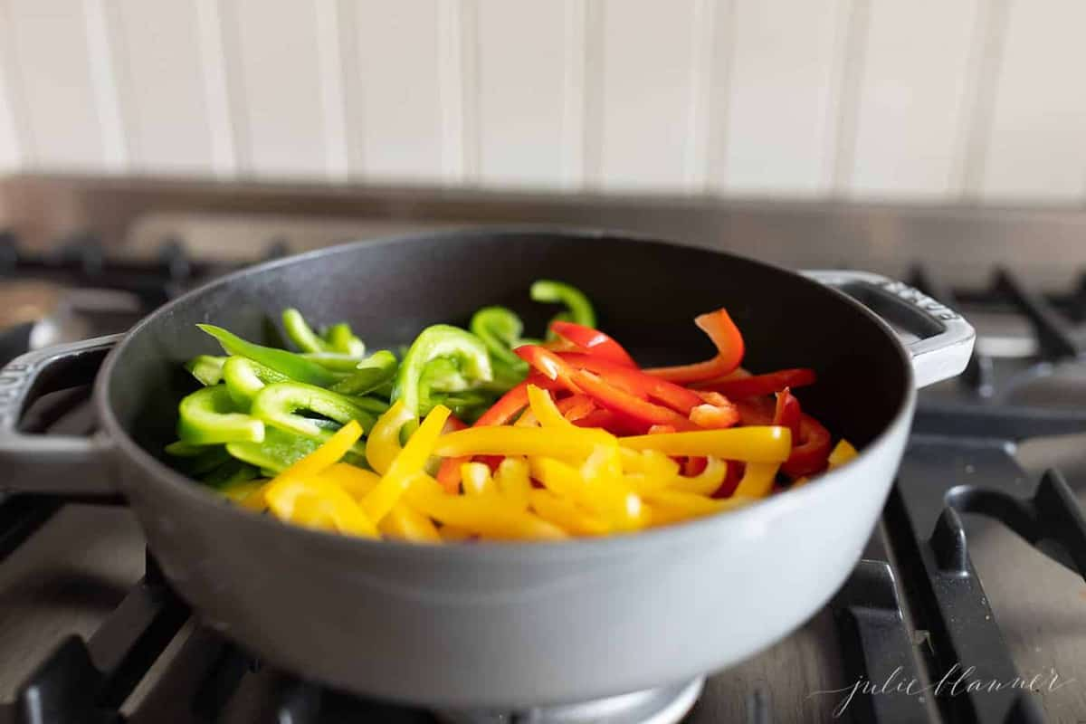 Red, green, and yellow bell peppers cut in a pan on the stovetop.